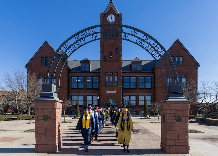 UCO graduates walking under Old North arch